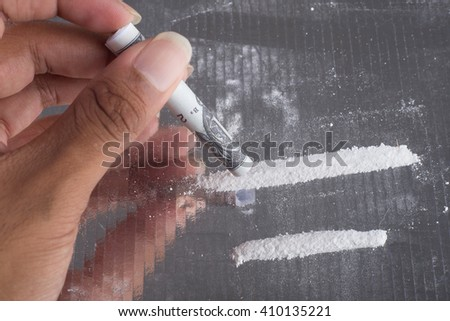 Man's hand with one hundred US dollars note to use cocaine - stock photo