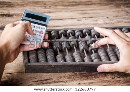 Man's hands accounting with old abacus and hold electronic calculator. picture financial concept