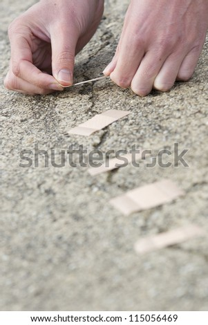 Man's hands applying adhesive bandage over cracks in the road. Vertical shot.
