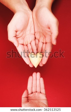Man's hands are giving little wooden heart to woman's hand - stock photo