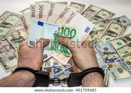 Man's hands are in metal handcuffs,holding money, on background of dollars  - stock photo