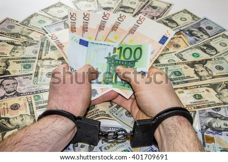 Man's hands are in metal handcuffs, holding money, on background of dollars - stock photo