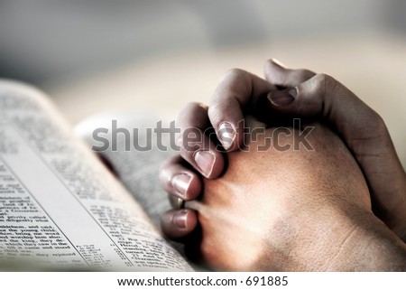 Man's hands clasped in prayer over a Holy Bible - represents faith and spirituality in everyday life. - stock photo