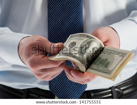 Man's hands counting dollar banknotes, closeup shot