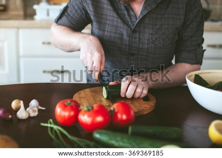 man's hands cut cucumber on the board for a vegetarian salad - stock photo