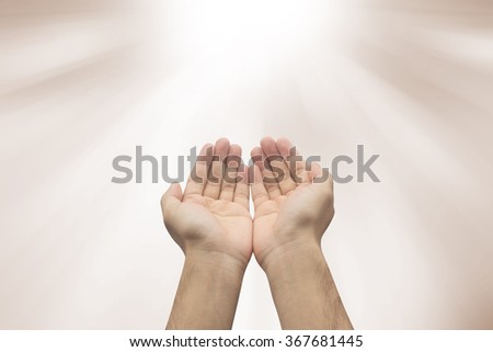 Man's hands gesture pray on blurred sepia brown ray beam background:assistance and support.love and caring concept.forgiveness and blessing conceptual.strength of human concept.helping and healing - stock photo