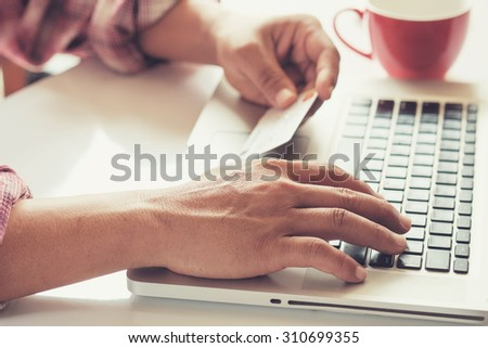 Man's hands holding a credit card and using pc or laptop for online shopping