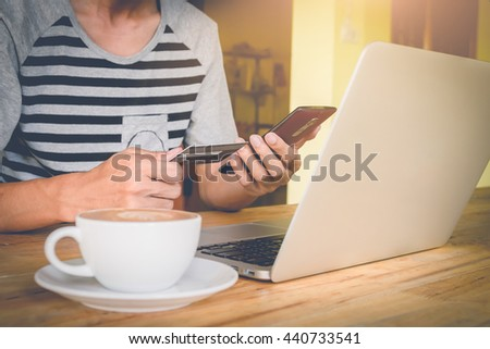 Man's hands holding a credit card and using smart phone and laptop for online shopping with vintage filter - stock photo