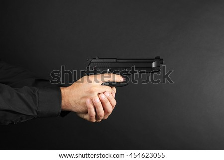 Man's hands holding gun on black background - stock photo