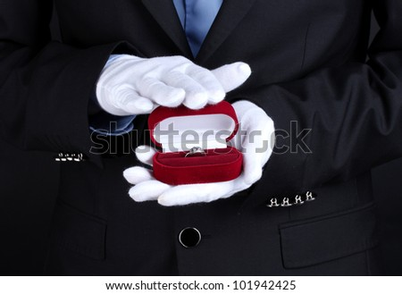 Man's hands holding ring in box - stock photo