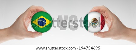 Man's hands holding styrofoam balls with Brazilian and Mexican flag against the white background. - stock photo