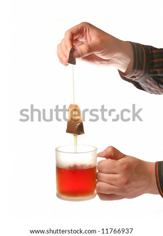 Man?s hands holding tea cup and teabag isolated on white background