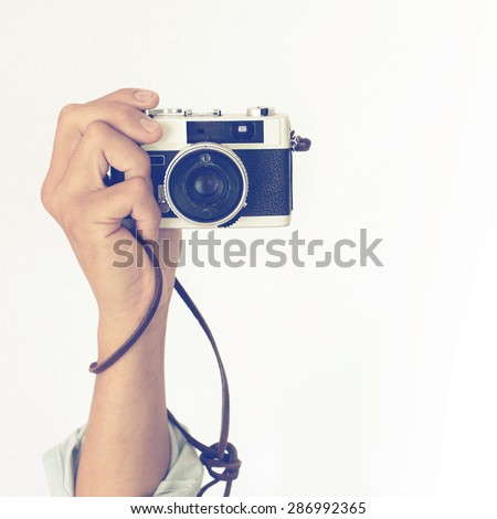 Man's hands holding vintage old camera with retro instagram filter effect  - stock photo