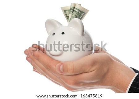 Man's hands holding white piggy bank with dollars inside isolated on white. - stock photo