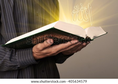 Man's hands holds Koran - holy book of muslims, shallow depth of field; inscription Allah in Arabic - stock photo