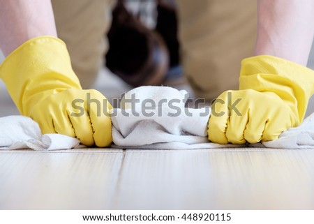 Man's hands manually cleaning the floor with white rag - stock photo