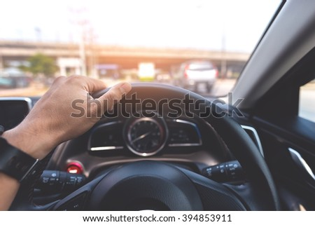 Man's hands of a driver on a modern car on the road. Vintage style processed - stock photo
