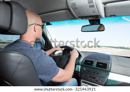 Man's hands of a driver on car