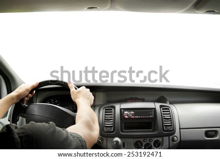 Man's hands of a driver on steering wheel of a minivan car  - stock photo