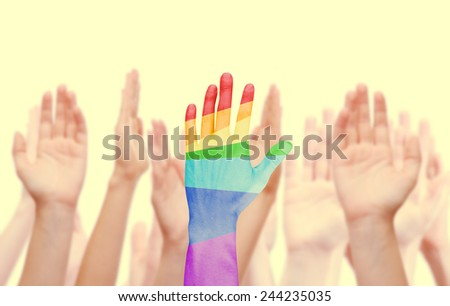 Man's hands painted as the rainbow flag on other hands background isolated on white - stock photo