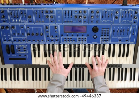 Man's hands playing the keyboard of a synthesizer - stock photo