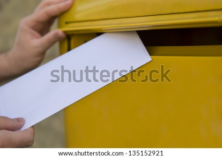 Man's hands posting a letter in a yellow post box - stock photo
