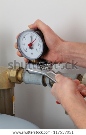 Man's hands screwing pressure gauge with wrench - stock photo