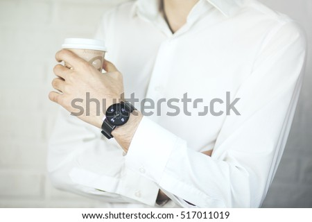man's hands standing at balcony with plastic cup