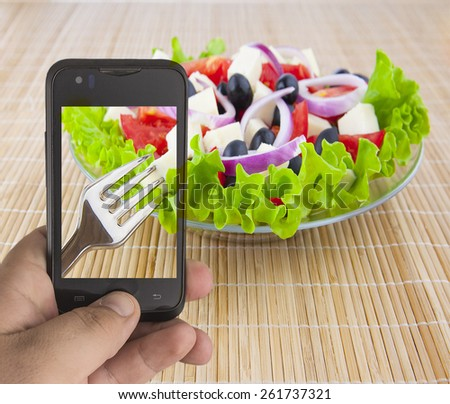 Man's Hands taking make photo  pictures vegetable vegan greek fresh healthy salad with red onion with smartphone Empty space for inscription Metal forl lie on dish glass transparent  plate  - stock photo