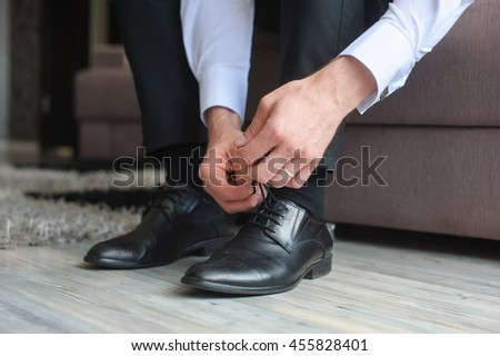 Man's hands tying shoelace of his new shoes.
