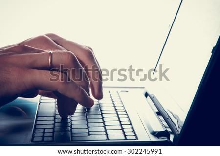 Man's hands typing on laptop keyboard. vintage - stock photo