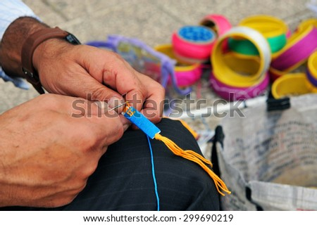 Man's hands weaving a bracelet. - stock photo