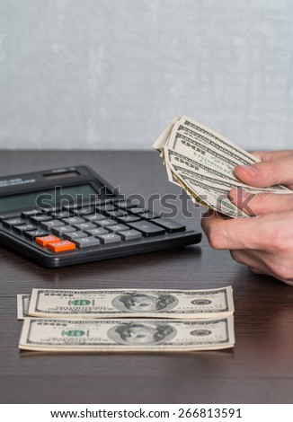 Man's hands with money and calculator. Money saving concept. - stock photo