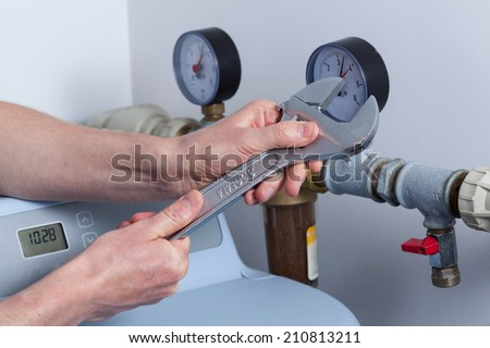 Man's hands with wrench repairing pressure gauge
