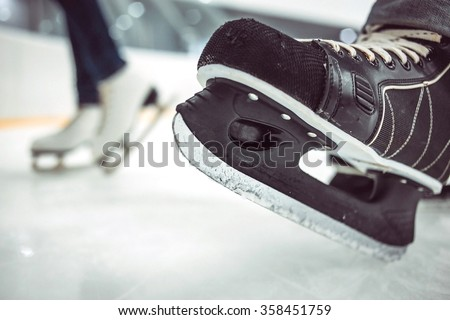 Man's hockey skates and women's figure skates on ice background - stock photo
