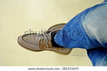 man's leg wearing jeans and brown shoes