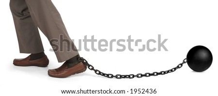 man's legs dragging a ball and chain - stock photo