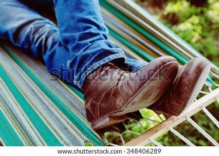 Man's legs in shoes lying in hammock - stock photo