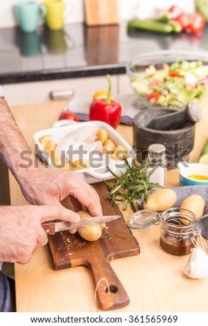 Man's or chef's hands preparing dinner (chicken drumsticks with potatoes) in a roasting dish - close up. Cooking - kitchen interior as background, food ingredients on table. - stock photo