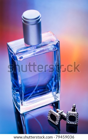 man's perfume and cufflinks in mixed light - stock photo