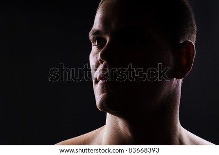 Man's portrait on black background. Close-up face