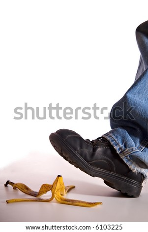 Man's shoe about to step on a banana peel and fall - stock photo