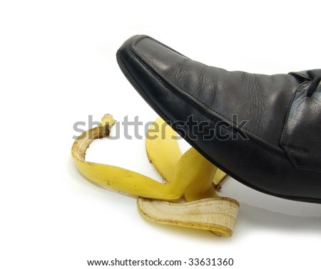 man's shoe about to step on a banana skin - stock photo