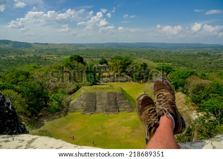 man's shoes overlooking xunantunich maya site ruins in belize caribbean - stock photo