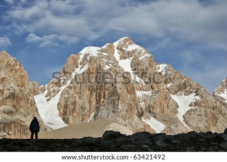Man's silhouette against the mountain peak - stock photo
