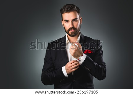 Man's style. Elegant young man getting ready. Dressing suit, shirt and cuffs - stock photo
