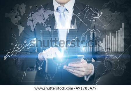 Man's torso with laptop. Graphs and world map are on blackboard. Concept of trading. Toned image. Double exposure. Elements of this image furnished by NASA