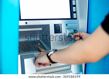Man's using the ATM machine with cash cards