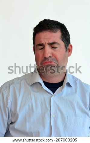 Man sad face expression. Male emotional expression on white background. Concept photo of sadness, disadvantage, loss, despair, helplessness and sorrow. - stock photo