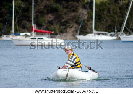 Man sails a rubber inflatable dinghy boat. - stock photo